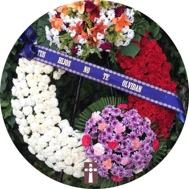 Corona. Clásica, en flor natural. Dimensiones: Aro de 90cm de diámetro con dos centros de flor variada.